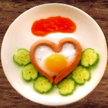 Heart shaped fried egg with sausage - romantic breakfast